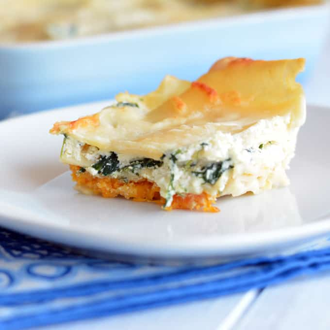 A slice of creamy three-cheese Butternut squash lasagna on a white plate.