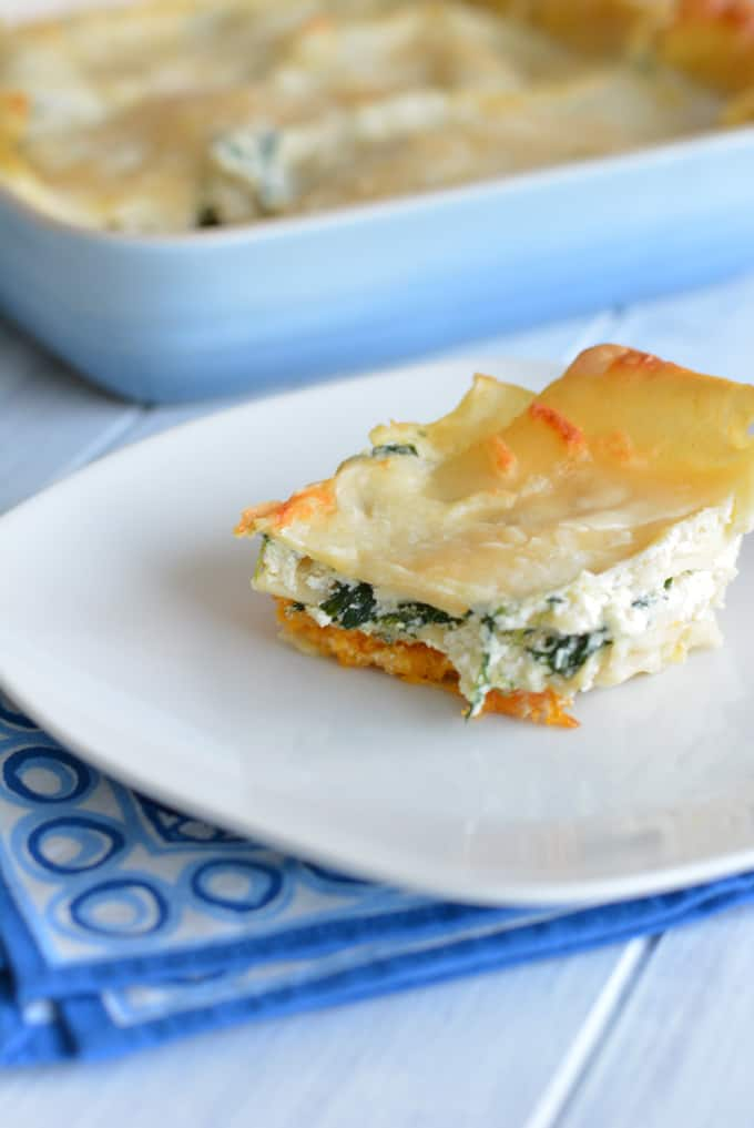 A slice of creamy butternut squash lasagna stuffed with three cheeses and fresh spinach on a white plate.