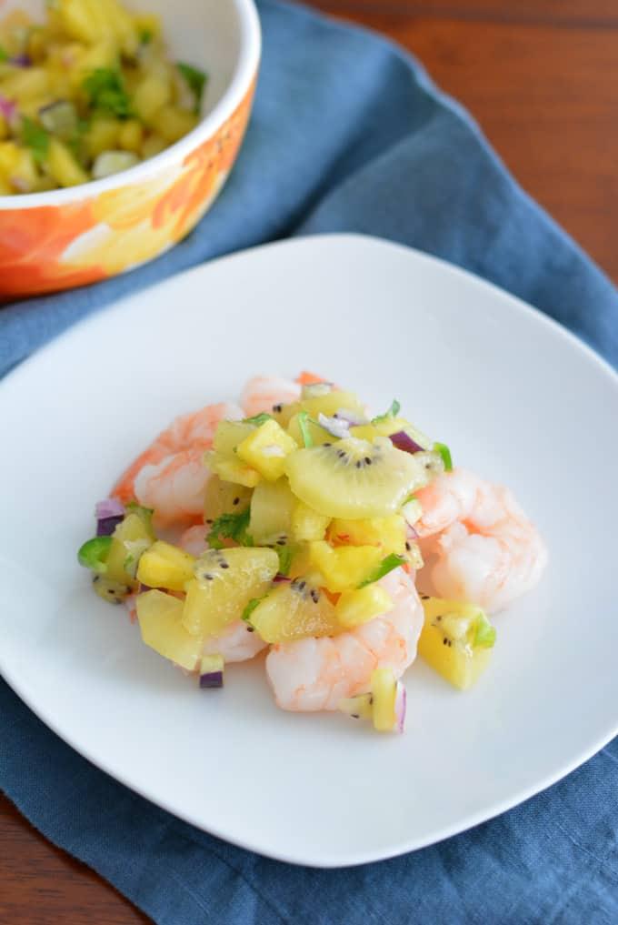 Kiwi pineapple fruit salsa on top of shrimp on a white plate.