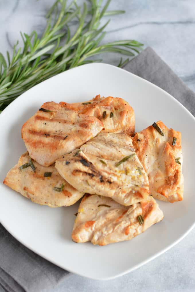 Grilled Lemon Rosemary Chicken Breast on a white plate.