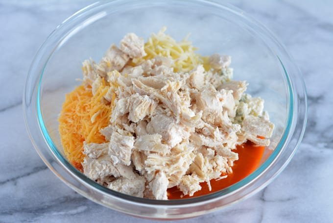 A bowl with chicken, cheese, and hot sauce to make baked buffalo chicken dip.