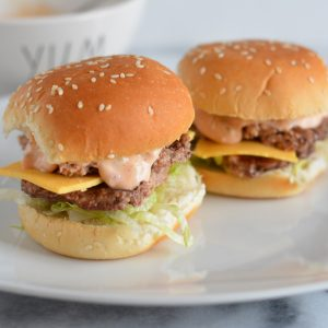 Mini cheese burgers on a plate.