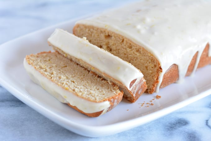 A glazed lemon loaf sliced on a white plate.
