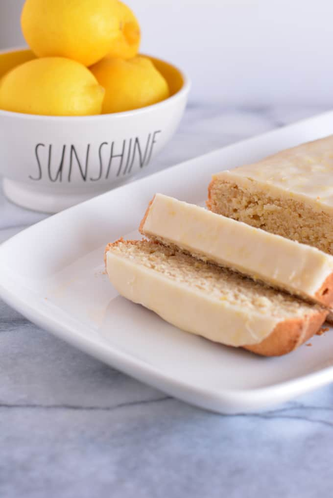 Glazed lemon loaf sliced on a white place with a bowl of lemons in the background